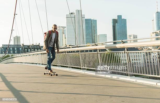 Germany, Frankfurt, man skateboarding on bridge