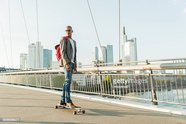 Germany, Frankfurt, man skateboarding on bridge