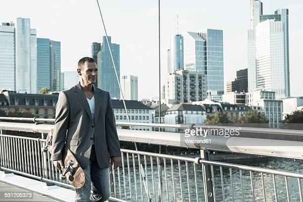 Germany, Frankfurt, man walking with skateboard on bridge over river Main