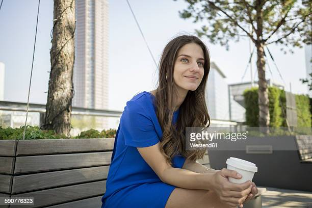 Germany, Frankfurt, portrait of smiling businesswoman sitting on a bench with coffee to go