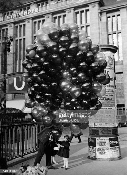 Germany Free State Prussia Berlin Man selling balloons is handing a balloon to a smal girl In the background the department store Wertheim can be...