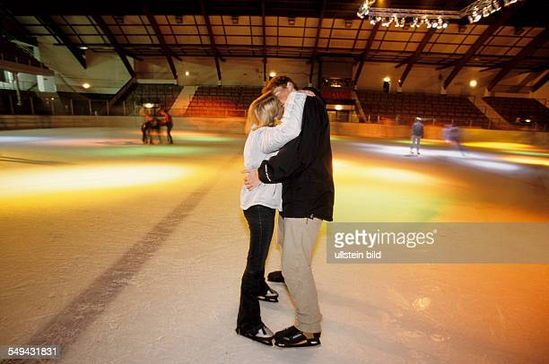 Free time A young couple skating in an iceskating rink they are kissing
