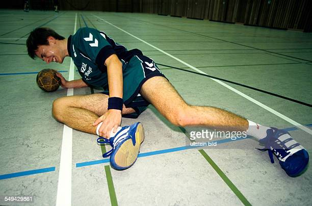 Free time Handball player he is injured and lieing on the floor