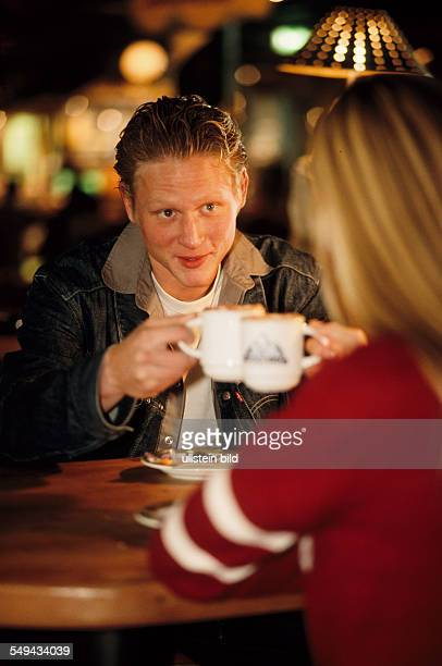 Free time Portrait of a young man he is sitting opposite to a girl they are drinking hot chocolate