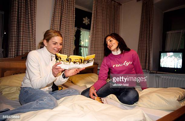 Free time Two friends in their skiing holiday their are sitting on the beds in their hotel room