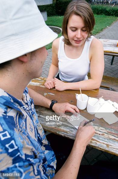 Free time Two young persons in a cafe the man is writing something on a piece of paper the woman is watching him