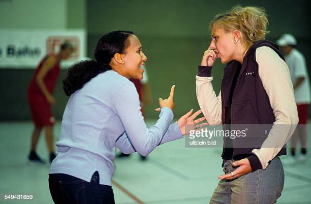 Free time Two young women in a gymnasium discussion