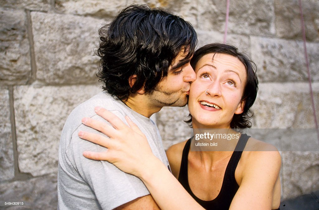 Free time.- Young persons after climbing; a man is kissing a woman on her cheek.