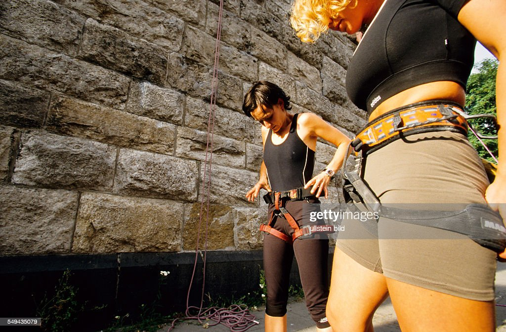 Free time.- Young women preparing for climbing; safety equipment.