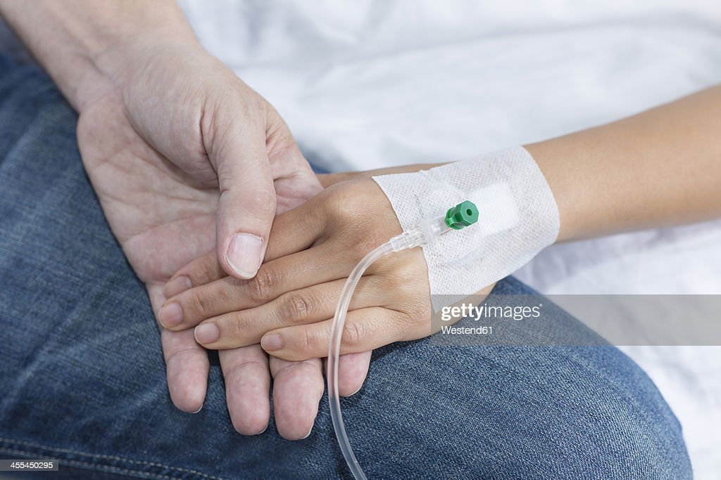 Germany, Freiburg, Woman holding hand of man in hospital, close up