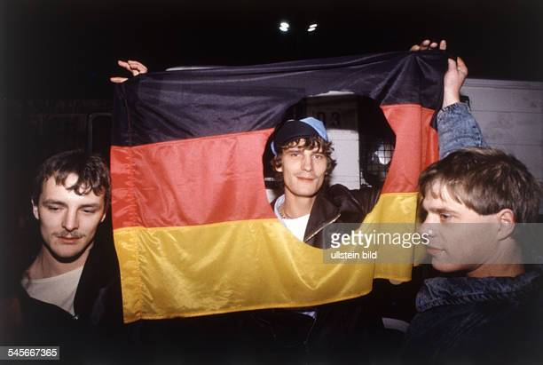 Germany / GDR Berlin The fall of the wall EastGerman teenagers cut out the symbols of hammer garland of corn and spring bow of the flag of the GDR...
