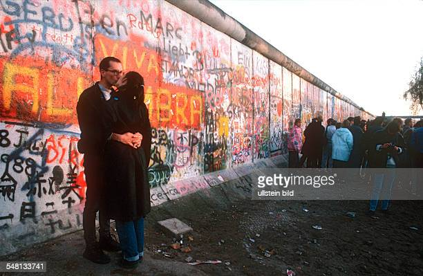 Germany / GDR Berlin The fall of the wall Installation of a new border crossing at Potsdamer Platz Pair of lovers on front of the wall 11/