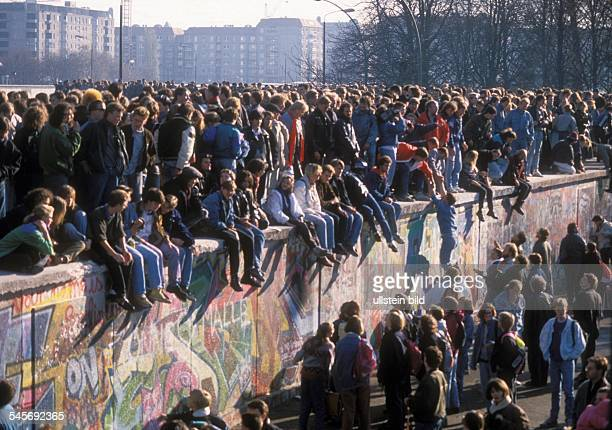 Germany / GDR Berlin The fall of the wall People on top of the wall at Brandenburg Gate