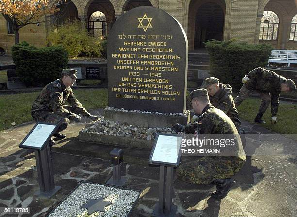 German army soldiers clean a memorial dedicated to Jewish victims of the so called 'Crystal Night' violence during which synagogues throughout...