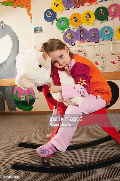 Germany, Girl (2-3) sitting on rocking horse holding teddy bear, portrait