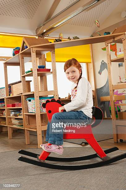 Germany, Girl (6-7) in nursery sitting on rocking horse, smiling, portrait