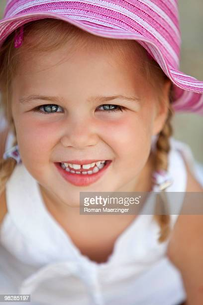 Germany, Girl (4-5) wearing sun hat, smiling, close-up, portrait