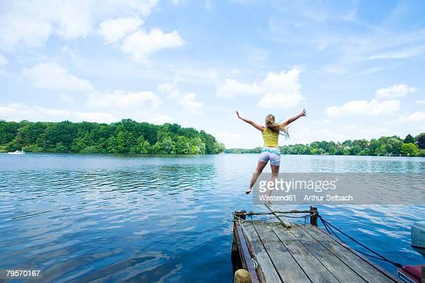 Germany, Griebnitzsee, woman jumping into lake, rear view