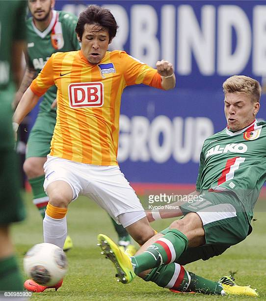 AUGSBURG Germany Hajime Hosogai of Hertha Berlin fights for the ball against FC Augsburg's Alexander Esswein in the first half of a soccer match in...