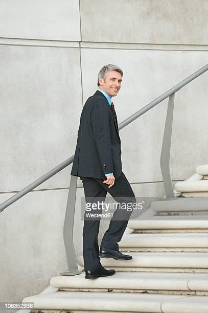 Germany, Hamburg, Businessman climbing steps, smiling, portrait