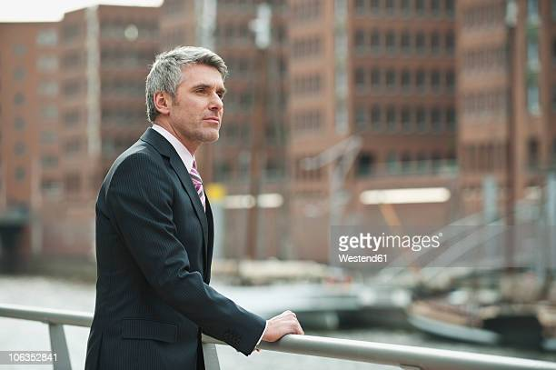 Germany, Hamburg, Businessman looking away at harbour