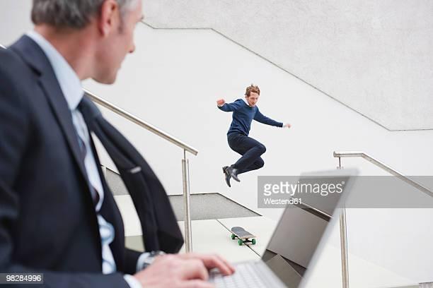 Germany, Hamburg, Businessman using laptop watching man skateboarding in background