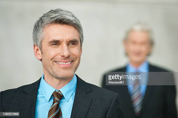 Germany, Hamburg, Businessmen, mature man smiling in foreground