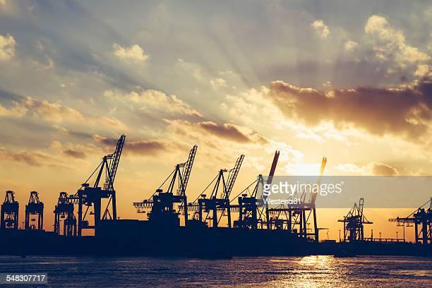 Germany, Hamburg, container cranes at sunset