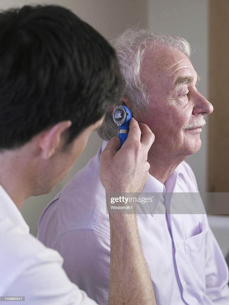 Germany, Hamburg, Doctor examining patient with otoscope : Stock Photo