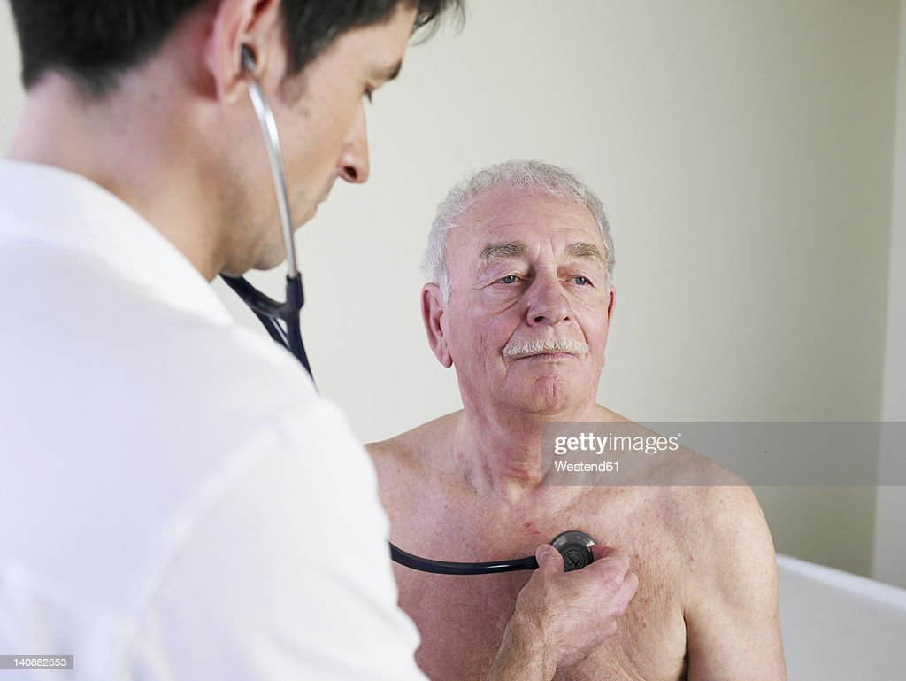 Germany, Hamburg, Doctor examining patient with stethoscope in clinic : Stock Photo