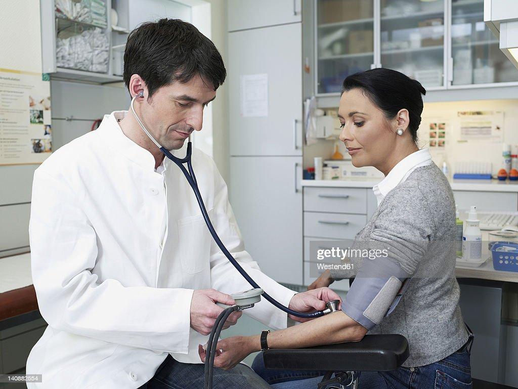 Germany, Hamburg, Doctor examining patient's blood pressure : Stock Photo