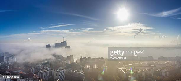 Germany, Hamburg, Elbphilharmonie and port sticking out of dense fog