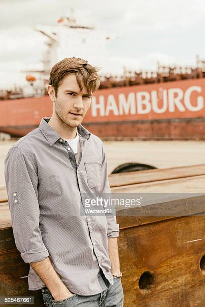 Germany, Hamburg, Hafencity, young man at harbor