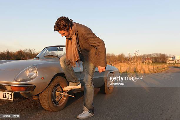 Germany, Hamburg, Man changing tyre of classic cabriolet car