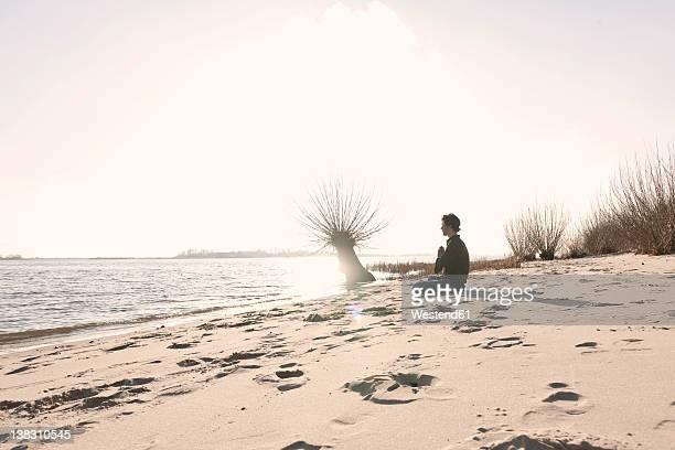 Germany, Hamburg, Man doing yoga exercise near Elbe riverside