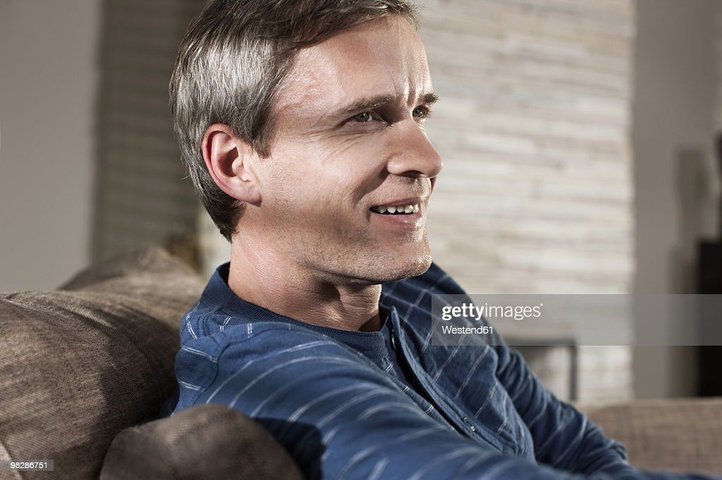 germany hamburg man sitting in living room side view closeup unknown getty images. Black Bedroom Furniture Sets. Home Design Ideas