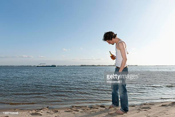 Germany, Hamburg, Man with beer bottle near Elbe riverside