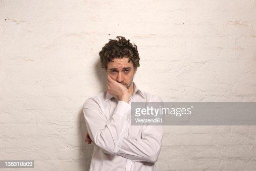 Germany, Hamburg, Mid adult man leaning against wall, portrait