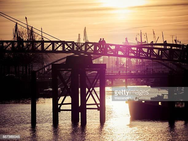 Germany, Hamburg, Port of Hamburg, Elbe river, Silhouettes of persons on bridge at sunset