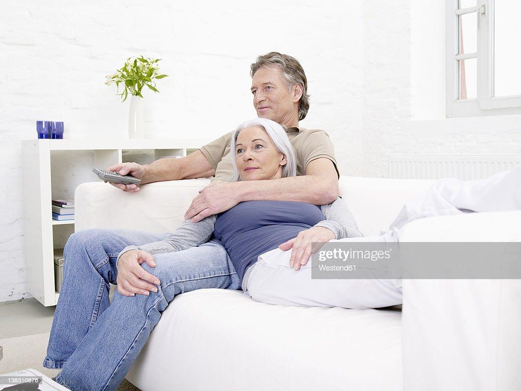 Germany, Hamburg, Senior couple watching tv