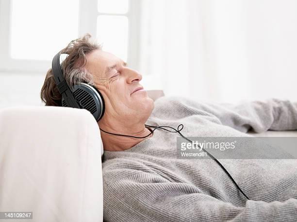 Germany, Hamburg, Senior man listening music with eyes closed