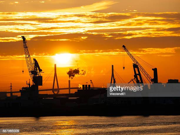 Germany, Hamburg, Silhouettes of harbour cranes at sunset, Koehlbrand bridge in the background