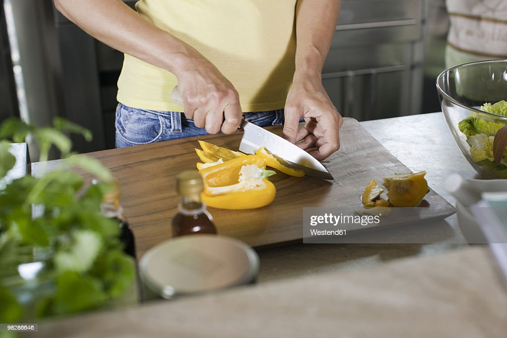 Germany, Hamburg, Woman cutting bell pepper : Unknown