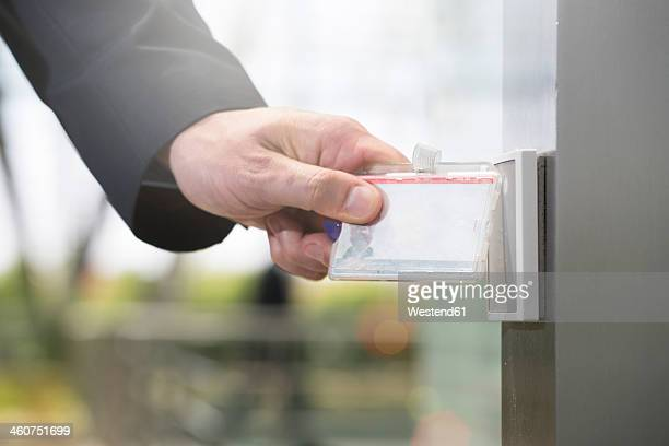 Germany, Hannover, Businessman using access card, close up