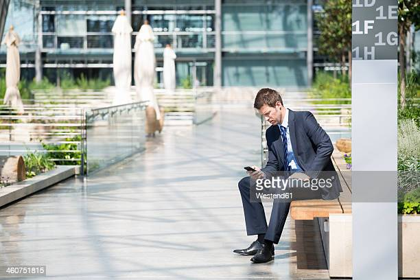 Germany, Hannover, Businessman using smart phone