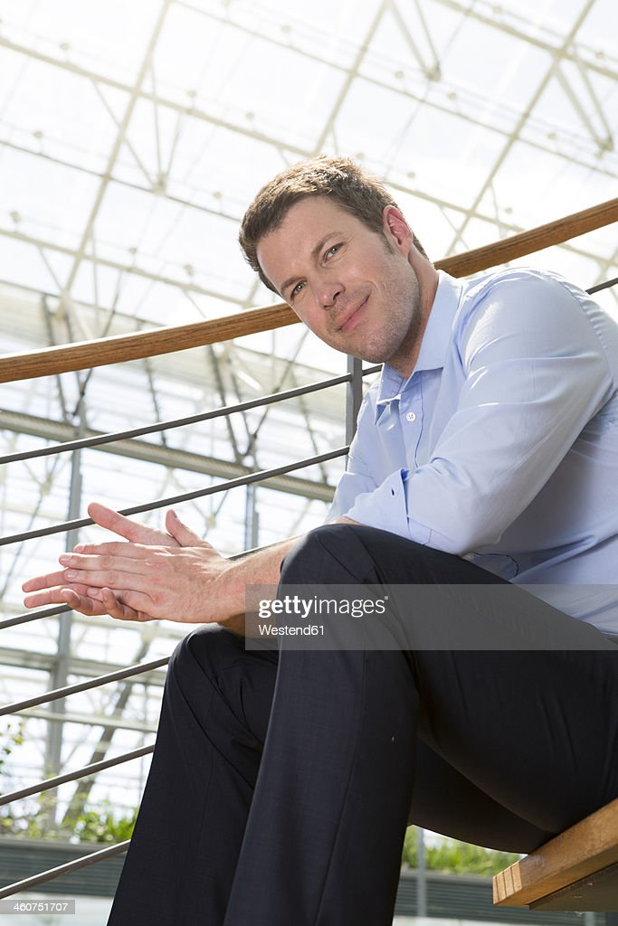 Germany, Hannover, Portrait of businessman sitting on stairs, smiling