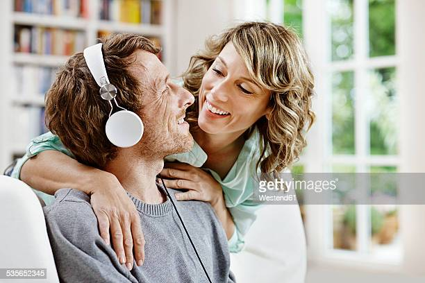 Germany, Hesse, Frankfurt, Adult couple at home listening to music