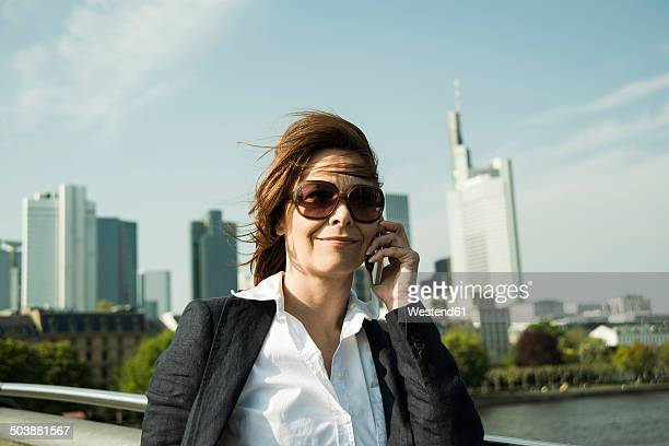 Germany, Hesse, Frankfurt, businesswoman telephoning with smartphone in front of skyline