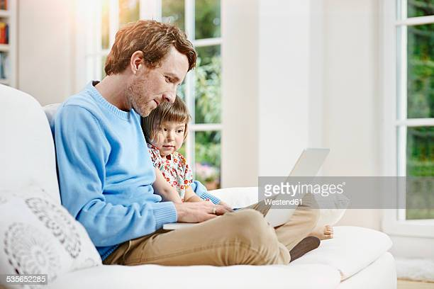 Germany, Hesse, Frankfurt, Father and daughter using laptop