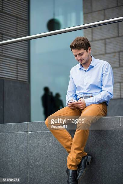Germany, Hesse, Frankfurt, portrait of sitting young man using his smartphone